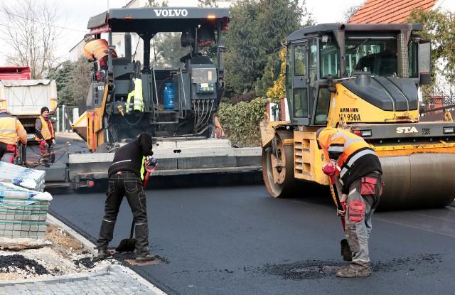 Wylewanie asfaltu na jezdni i ścieżce rowerowej ulicy Jackowskiego w Grudziądzu.