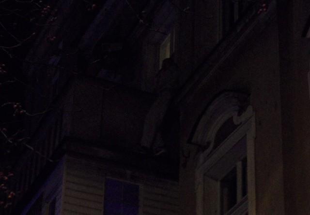 Na gzymsie przy balkonie, na 2. piętrze kamienicy w Grudziądzu stoi zdesperowany mężczyzna