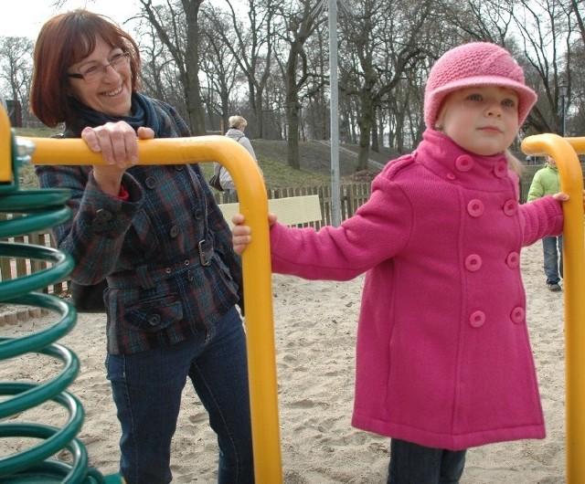 Trzyletnia Nadia bawi się na jednej z huśtawek. W parku opiekuje się nią babcia Jolanta.