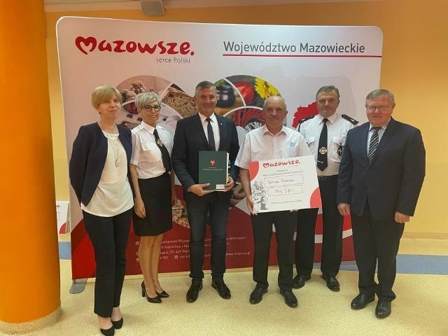 Wójt Rusinowa Marian Wesołowski z symbolicznym czekiem otrzymanym od samorządu Mazowsza.