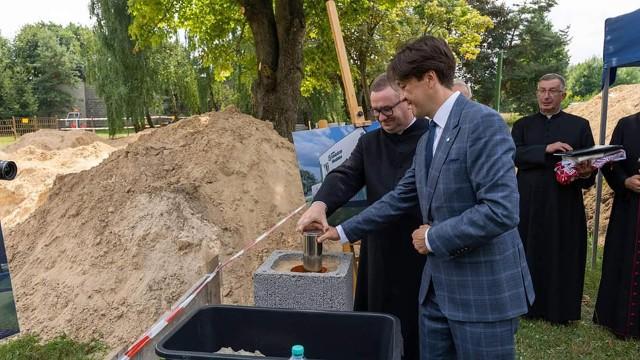 Piotr Kozłowski i ksiądz Tomasz Pastuszka włożyli akt erekcyjny w metalowym pojemniku do urny.