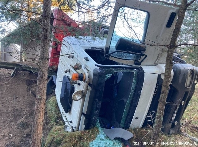 Auto z naczepą pełną piasku przewróciło się na bok. Kierowca, z urazem nogi, trafił do szpitala. Ciężarówka tarasowała drogę przez kilka godzin.