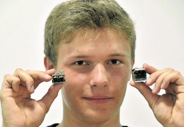 Piotr Wasilewski ma 18 lat. Jest uczniem II klasy  matematyczno-fizycznej. Na zdjęciu prezentuje skonstruowane przez siebie roboty nanosumo