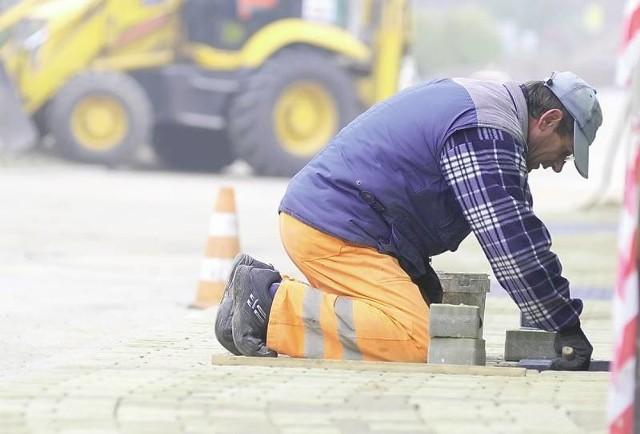 Tadeusz Szydłowski z firmy Melbud układa chodnik przy ul. Klonowej, na której niedawno został położony asfalt.