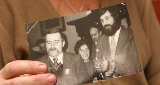 Córka opozycjonisty trzyma jego zdjęcia z Lechem Wałęsą.