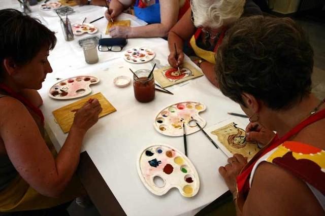Uczestnicy warsztatów podczas malowania. Zajęcia rozpoczynają się od poszukiwań wizerunków aniołów na ikonach i ściennych malowidłach.