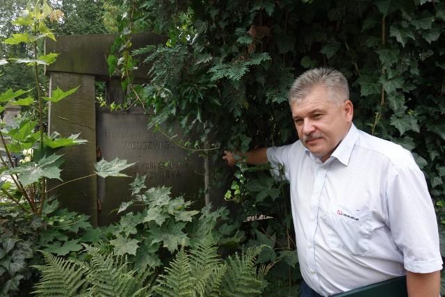 Prezes Cezary Pawlak przy zakrytym tują i bluszczem nagrobku Józefa Wolczyńskiego