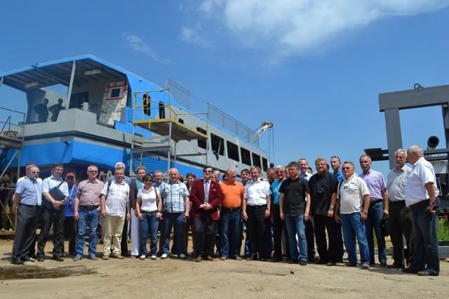 """Oto pełna delegacja, która odwiedziała w poniedziałek 17 czerwca stocznię, gdzie trwa budowa statku """"Zefir""""."""