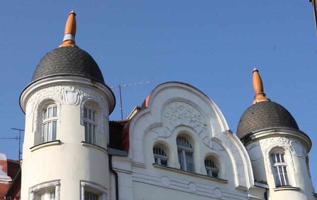 Lewa szpica na dachu kamienicy jest wyraźnie przechylona.