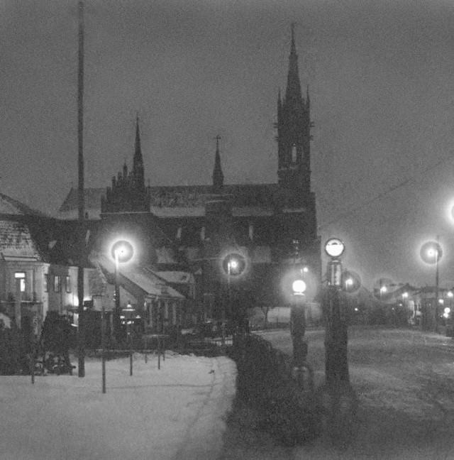 """Fotografia """"Rynek Kościuszki w nocy- przy oświetleniu lamp elektrycznych"""" wykonana w 1931 roku przez Sekcję Miłośników Fotografii przy Szkole Handlowej."""