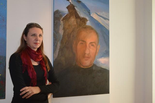 Marta Makarczuk przy jednym z portretów ks. Krzysztofa Grzywocza.