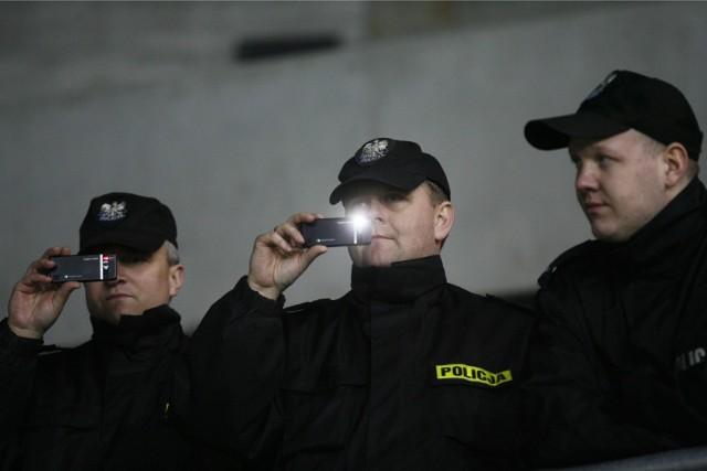Policjanci sprawdzają za pomocą telefonów, czy kontrolowane osoby są w domach.