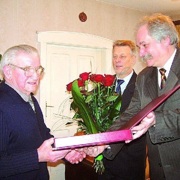 Zygmunt Przybylak odbiera pamiątkowy grawerton z rąk  przewodniczącego Rady Miejskiej Nakła Andrzeja Jedynaka.  Chwilę potem kwiatami obdarował  jubilata Zenon Grzegorek,  burmistrz Nakła.