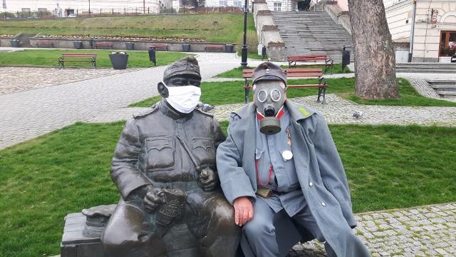 Józef Szwejk, towarzyszący mu piesek, a także niedźwiadki noszą maski ochronne. Nieliczni ludzie przechodzący przez Rynek robią zdjęcia nietypowo wyposażonym pomnikom.