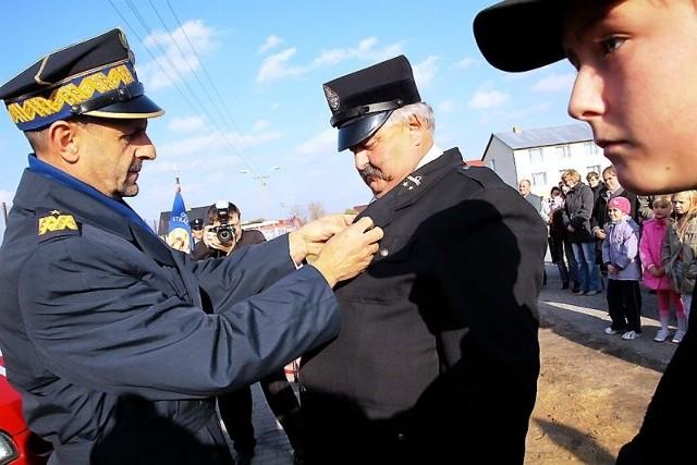 Brązową odznakę prezesowi OSP Tadeuszowi Juraszewskiemu wręcza generał Marek Kowalski.