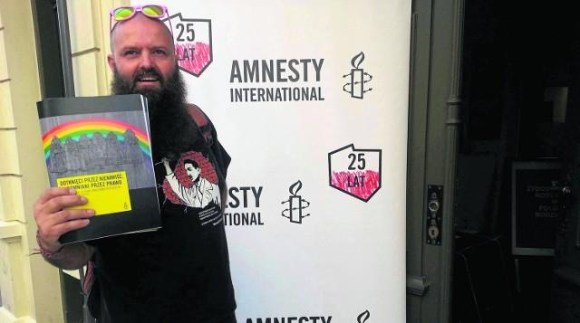 Dariusz Paczkowski, prezes Fundacji Klamra, z raportem Amnesty International