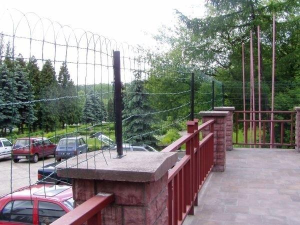 Na murowanym ogrodzeniu postawiono niski metalowy płotek, który wygląda jak zasieki.