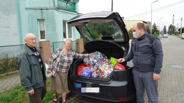 Maria Szydłowska, mieszkanka Jachcic, już po raz czwarty przekazała nakrętki dla małego Bartka. Pan Radosław (w maseczce), tata chłopca, był pod wrażeniem, bo seniorce udało się zebrać aż 60 kg nakrętek. W ich załadowaniu do auta pomagał sąsiad pani Marii.