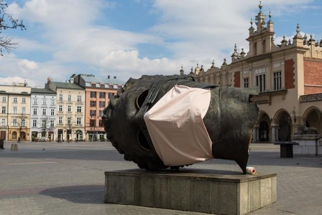 Najważniejsze symbole roku pandemii w Polsce - pusty Rynek Główny w Krakowie oraz maseczka. Tu na rzeźbie Igora Mioraja