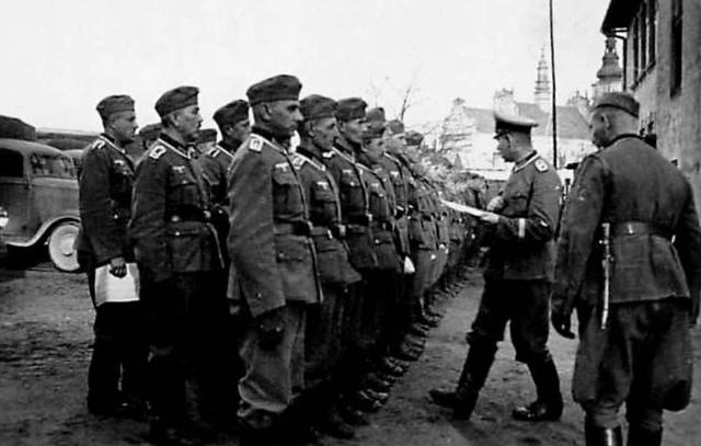 Tarnobrzeg, lata 1939-1941 , żołnierze Wermachtu na tyłach budynku szkolnego. W tle sylwetka kościoła Wniebowzięcia NMP.