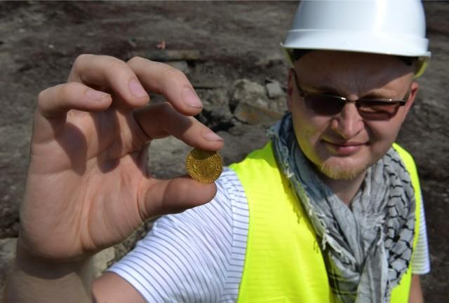 Archeolog Jakub Prager demonstruje znalezioną złotą monetę. To pierwsze takie znalezisko w Gdańsku