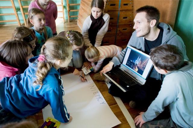 Student opowiada o zaletach programu Erasmus swoim młodszym kolegom w szkole podstawowej - zdjęcie ilustracyjne