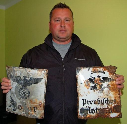 Przemysław Żydałowicz pokazuje dwie tablice z hitlerowskimi symbolami odkopane w centrum Szczecinka.