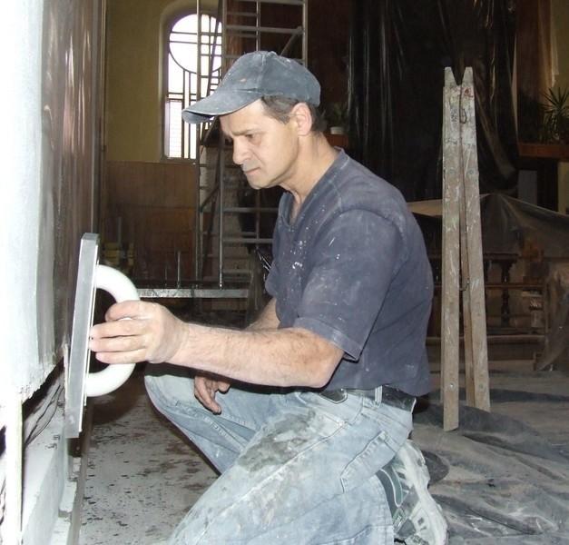 Pan Zbyszek remontuje wnętrze kościoła św. Barbary. Równa ściany po założeniu wzmocnień