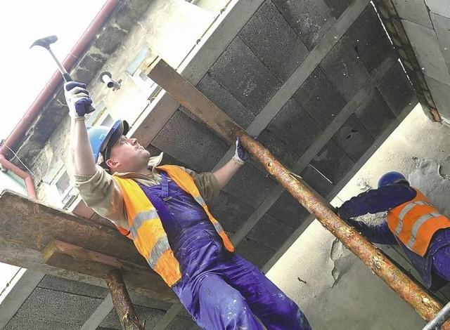 Pan Tomek pracuje przy odnowie elewacji teatru