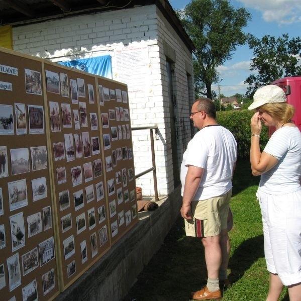 """Obok sceny ustawiono tablice z archiwalnymi zdjęciami Krynek. Wystawę zatytuowano """"Znalezione w szufladzie - Krynki w starej fotografii""""."""