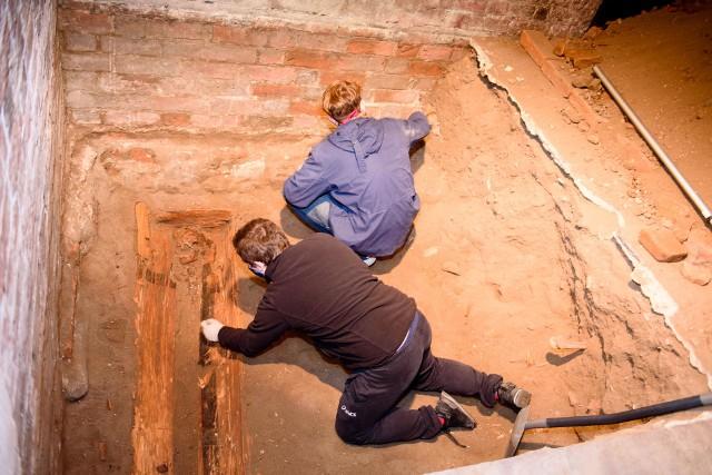 Toruński kościół świętego Jakuba jest bez wątpienia jedną z najpiękniejszych i najbardziej fascynujących świątyń gotyckich w kraju. Dla badających go naukowców, kopalnią ciekawostek i tajemnic. Jego otoczenie toruńscy archeolodzy badają już od lat.Zobacz też:Tak przez 100 lat zmieniał się plac RapackiegoRemont tężni w Ciechocinku. Mamy zdjęciaSzukali tam m.in. śladów klasztoru, przejścia podziemnego z położonego po drugiej stronie ulicy szpitala (zamurowane wejście widzieliśmy w bardzo głębokiej szpitalnej piwnicy w 2017 roku), przebadali także cmentarz - świątynię otacza bowiem poświęcona ziemia, w której mieszkańcy toruńskiego Nowego Miasta chowani byli od średniowiecza do przełomu XVIII i XIX wieku.Tym razem przenieśli się z badaniami do wnętrza kościoła. To pierwsze takie wykopaliska pod sklepieniem kościoła św. Jakuba od kilkunastu lat. Archeolodzy założyli dwa sondażowe wykopy szukając m.in. pozostałości dawnych posadzek i odpowiedzi na pytania - jak i z czego były one ułożone?