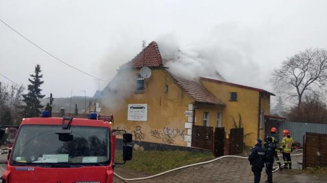 Trwa akcja gaszenia pożaru w domu przy ul. Kilińskiego. Działają zastępy strażaków z KP PSP w Chełmnie, a także z OSP w Brzozowie, Podwiesku i Chełmnie.Ogień pojawił się około godz. 9. Mieszkańcy natychmiast ewakuowali się sami z budynku.- Po dojeździe na miejsce  zdarzenia zastano pożar budynku wielorodzinnego - mówi kpt.inż. Artur Tokarczyk, zastępca dowódcy Jednostki Ratowniczo-Gaśniczej w KP PSP w Chełmnie. - Właścicielka oraz 10-letnia dziewczynka ewakuowały się przed przybyciem Jednostek Ochrony Przeciwpożarowej. Pożarem objęte było jedno z pomieszczeń na poddaszu. Konstrukcja budynku była murowana, stropy drewniane, a dach - także drewniany, pokryty dachówką ceramiczną. Było duże zadymienie. Nikt nie został poszkodowany. Strażacy zabezpieczyli miejsce zdarzenia, odcięli dopływ prądu i gazu do budynku. W pierwszej fazie rozwoju pożaru, ratownicy w aparatach ochronnych podali jeden prąd wody na źródło ognia. Spenetrowali wszystkie pomieszczenia. Innych osób nie stwierdzili. - Wprowadzono drugą rotę z linią wężową. Zlokalizowane zostało źródło ognia w stropie  budynku pomiędzy parterem a poddaszem - dodaje Artur Tokarczyk. - Przy użyciu pił do cięcia drewna wycięte zostały otwory. Przelano wodą. Nadpalone elementy wyposażenia pomieszczeń wyrzucone zostały na zewnątrz budynku. Zadysponowane zostały dodatkowe siły i środki w celu zabezpieczenia butli z powietrzem ze względu na duże zadymienie. Zorganizowane zostało zaopatrzenie wodne z sieci hydrantowej - hydrant znajdował się w odległości około 400 metrów. Po zlokalizowaniu pożaru strażacy przystąpili do dogaszania. Wezwany został powiatowy inspektor nadzoru budowlanego, który wyłączył z użytkowania pomieszczenia objęte działaniami gaśniczymi. Miejsce zdarzenia przekazano właścicielowi, któremu zalecono wykonać przegląd instalacji elektrycznej przed rozpoczęciem użytkowania pomieszczeń. Strażacy zalecili także wietrzenie pomieszczeń oraz nadzór nad budynkiem.