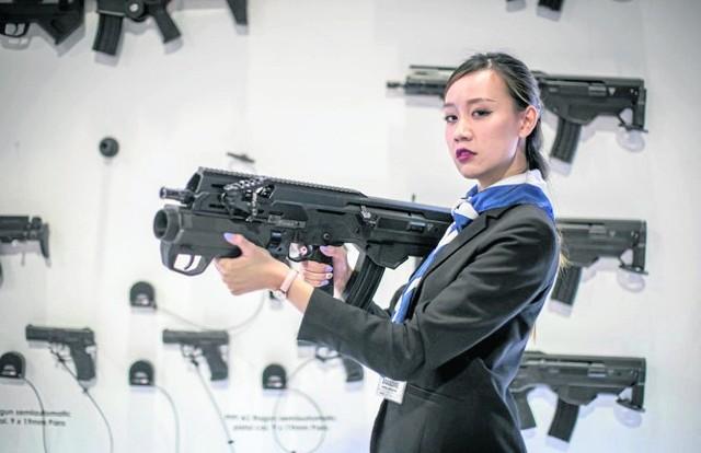 Indonezyjska hostessa prezentuje wyprodukowany w Radomiu karabinek automatyczny msbs Grot w wersji z granatnikiem.