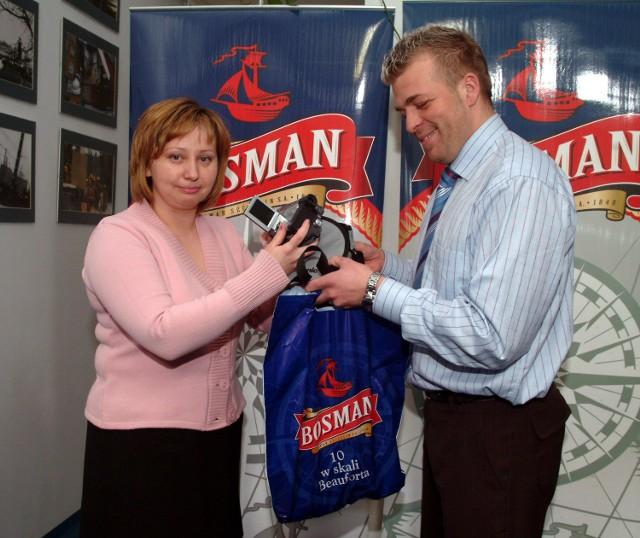 Przedstawiciel Bosmana Browaru Szczecin, fundatora nagrody, wręcza Hannie Piecyk kamerę cyfrową.