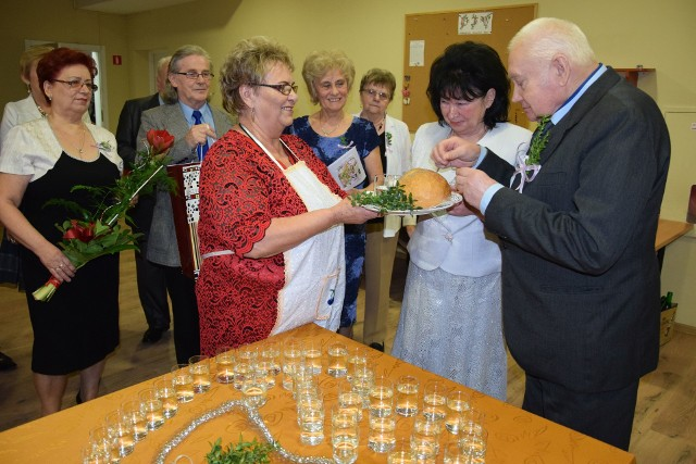 """Seniorzy z klubu """"Wrzos"""" nowożeńców przywitali tak, jak tradycja nakazuje - chlebem i solą, panu Zenonowi i pani Genowefie złożyli też moc gorących życzeń i pomyślności na dalsze lata życia"""