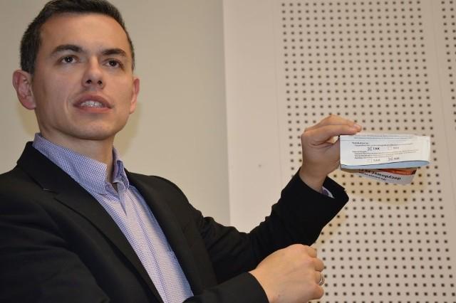 Kamil Kaczmarek z ulotką zachęcającą do głosowania i pokazującą, na jakie pytania trzeba odpowiedzieć