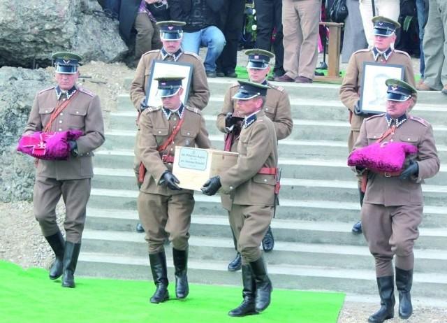 Członkowie Grupy Rekonstrukcyjnej Szkoły Podoficerskiej Korpusu Ochrony Pogranicza z Osowca–Twierdzy znoszą trumnę ze szczątkami bohaterów.