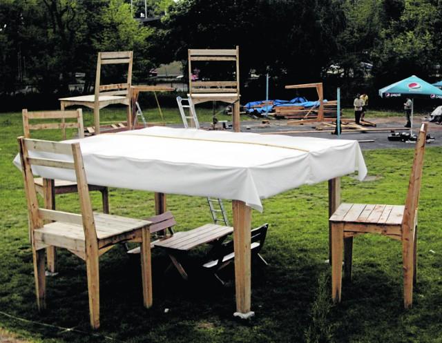 """Na tym stole spokojnie zmieściłby się największy na świecie  schabowy. Wysokie na kilka metrów drewniane stoły przykryte obrusami oraz gigantyczne krzesła stanęły już w Sopocie, na  terenie Baru """"Sopocki Zdrój"""", niedaleko hotelu Mera Spa (ul. Bitwy pod Płowcami 61). Tuż pod tymi gigantycznymi meblami znajdują się mniejsze, dopasowane do """"ludzkich"""" rozmiarów."""