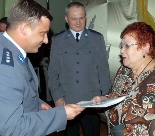 Pani Ela obiera list gratulacyjny z rąk zastępcy powiatowego komendanta Ireneusza Winnickiego. W środku stoi szef komisariatu z Pełczyc asp. Gerard Sopiński.
