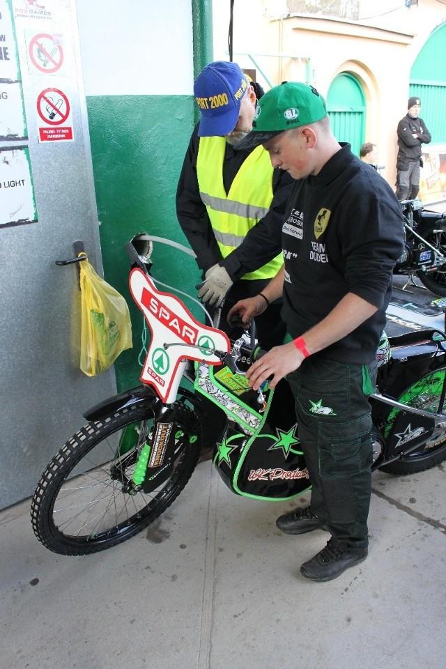 Kacper Rogowski tankuje motocykl Patryka Dudka