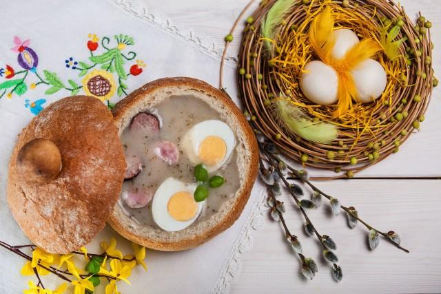Składniki:-2 szklanki zakwasu (skórka od chleba, 25 dag mąki pszennej, 1 l wody)-1 ząbek czosnku-2 łyżki chrzanu-¾ szklanki śmietany-3 szklanki bulionu drobiowego -rzeżucha-4 jajka-biała kiełbasaSposób przyrządzenia: Dwa dni wcześniej przygotować zakwas: 25 dag mąki pszennej wymieszać z 1 l przegotowanej ciepłej wody, na wierzchu położyć skórkę od chleba i odstawić w ciepłe miejsce na 24 – 48 godzin.Do zakwasu wlać bulion drobiowy Vegeta, dodać czosnek i chrzan, doprowadzić do wrzenia. Następnie dodać śmietanę i w razie potrzeby przyprawić do smaku. Dodać białą kiełbasę pokrojoną w plasterki. Zupę przed podaniem udekorować gałązkami rzeżuchy, podawać z jajkami ugotowanymi na twardo.