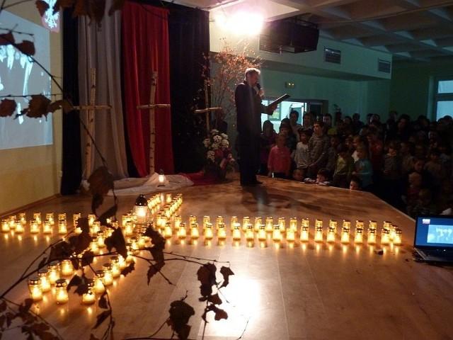 Wicedyrektor Marian Wikiera przy płonącym na scenie krzyżu opowiadał młodzieży o tragicznie zmarłym Pośle Przemysławie Gosiewskim, który wielkorotnie gościł w szkole.