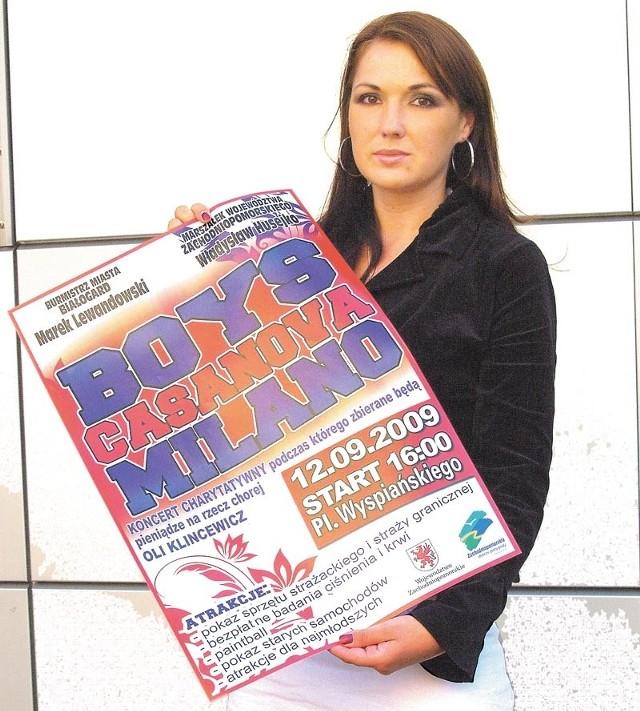 Małgorzata Chir z Urzędu Miasta w Białogardzie z plakatem zapraszającym na koncert.