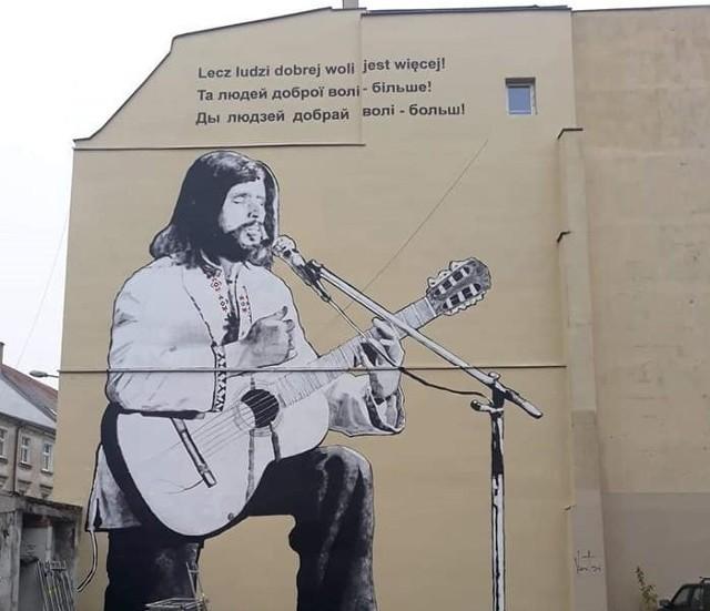 """Mural """"Czesia z Grobli"""", jaki od niedawna znajduje się na kamienicy przy ulicy Grobla 27 w Poznaniu, przedstawia legendarnego wokalistę i muzyka Czesława Niemena, ubranego w ukraińską koszulę i śpiewającego znamienne słowa z piosenki """"Dziwny jest ten świat"""": """"lecz ludzi dobrej woli jest więcej"""" w języku polskim, białoruskim i ukraińskim."""