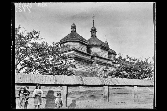 Dzieci na tle cerkwi pod wezwaniem św. Michała w miejscowości Tłuste. Budynek został wzniesiony w 1713 r., a rozebrany w 1911. Z kolei w 1921 roku zbudowano murowaną cerkiew, pod tym samym wezwaniem, projektu Jana Sas-Zubrzyckiego, urodzonego właśnie w tej miejscowości. Zdjęcie wykonane w 1907 roku.