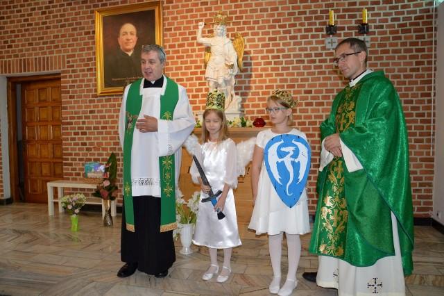 Dziewczynki przebrane za świętego Michała Archanioła z księżmi przy figurze Księcia Wojska Niebieskiego