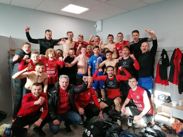 Triumfujący piłkarze i sztab szkoleniowy Bytovii Bytów po meczu w Elblągu