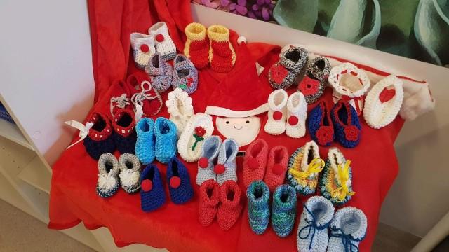 """Wolontariusze z programu """"Senior maluszka tuli"""" zaangażowali się w akcję tworzenia bucików dla dzieci z Oddziału Noworodkowego Szpitala Miejskiego im. F. Raszei."""