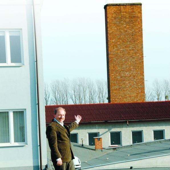 Bogusław Łącki, prezes APS, na dachu hali, którą chciałby podwyższyć o dwa piętra. W tle - budynek o takiej właśnie wysokości. APS nie dostała jednak zgody na nadbudowę.