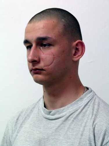 Piotr Korcala. Groźny przestępca z Krakowa uciekł ze szpitala psychiatrycznego. Ma charakterystyczną bliznę na policzku i tatuaże.